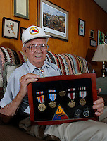 NWA Media/DAVID GOTTSCHALK - 8/27/14 - Quenton Skelton displays his World War II medals at his Springdale home Wednesday August 27, 2014. Skelton served in the Armored Division.