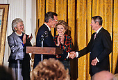 United States President George H.W. Bush shakes hands with former U.S. President Ronald Reagan as he officiates at the presentation of the official portraits of President Reagan and first lady Nancy Reagan  in the East Room of the White House in Washington, D.C. on November 15, 1989.  From left to right: Barbara Bush, President Bush, Nancy Reagan, former President Reagan..Credit: Ron Sachs / CNP