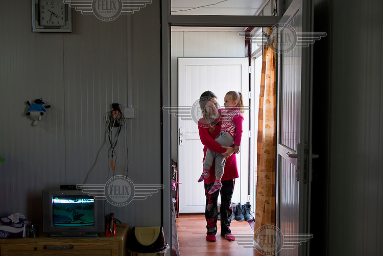 A four year old Yazidi girl and her mother in theri temporary accommodation in a refugee camp near Dohuk. <br /> She was captured by Islamic State (IS) with her parents on 3 August 2014 when IS invaded the town of Sinjar. They were taken to Syria and then back to Iraq and spent 3 months in captivity. When they were living in Kocho village one of the IS fighters told her father that his son wants to marry her. Her father decided to escape and on 22 December while people were being loaded into cars for a transport the girl and her parents escaped. Soon after the girl became ill and her father had to flag down a car, though this was risky, and ask the driver to take them. The driver recognised them and took them to his home and gave them food. Then they were taken to near Sinjar mountain. They climbed the mountain and were met by Kurdish Peshmerga fighters. The girl still says 'The IS fighter is coming to take me away' sometimes and she hides when there are cars coming to the camp where the family is now living.