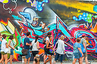 A walking tour visits the murals in the Bushwick neighborhood of Brooklyn in New York on Saturday, August 16, 2014.   The neighborhood is undergoing gentrification changing from a rough and tumble mix of Hispanic and industrial to a haven for hipsters and a destination for tourists, forcing many of the long-time residents out because of rising rents. (©Richard B. Levine)