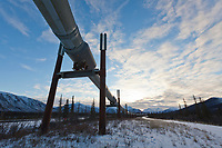 Trans Alaska oil pipeline traverses the winter tundra of the Brooks range mountains in the distance.