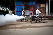 A padestrian looks on while a civic worker fumigates the streets to prevent the spread of malaria and dengue fever in New Delhi, India.