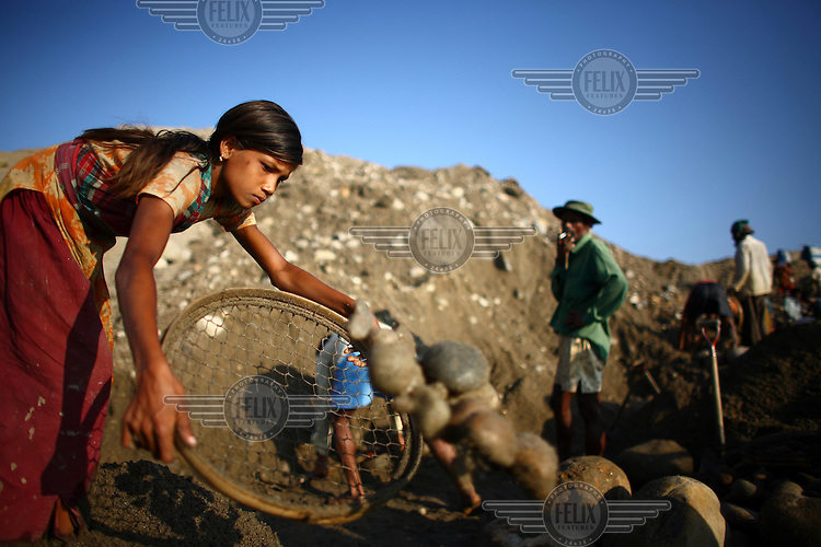 A girl sorts stones at Bhollar Ghat. At least 10,000 people, including 2,500 women and over 1,000 children, are engaged in stone and sand collection from the Bhollar Ghat on the banks of the Piyain river. Building materials such as stone and sand, and the cement which is made from it, are in short supply in Bangladesh, and commands a high price from building contractors. The average income is around 150 taka (less than 2 USD) a day.