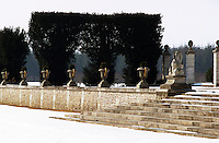 A row of stone urns with gilded handles lines a wall of the garden