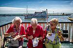 Nederland,Volendam, 05-08-2015  Tourists during the summer holiday in the historical part of Volendam. Elderly ladies enjoy see food. FOTO: Gerard Til / Hollandse Hoogte.