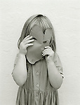 A three year old girl holds a home-made mask in front of her face, depicting a mouse.<br /> [This photograph is currently licensed through GalleryStock - please contact the photographer for details]