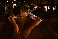 Waiting for the cattle showmanship competition at Minnesota's Nobles County Fair, Chris Tiesler leans on his bovine partner. Contestants are judged on poise and how carefully they manage their groomed animals. They are also judged on how quickly they respond to the judges instructions.