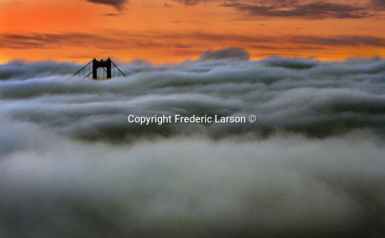 The San Francisco fog slowly rolls under the Golden Gate Bridge as it steams down the Marin headlands during the early morning twilight hours.