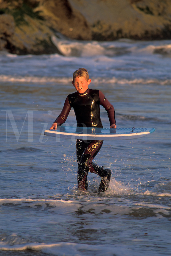 Young boy in wetsuit carries boogie board while walking through the surf along the beach, Santa Cruz, California.