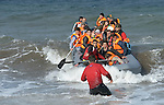 Refugees arrive in a rubber boat on a beach near Molyvos, on the Greek island of Lesbos on October 31, 2015.  They were received by local and international volunteers, one of whom is helping guide them through the surf, then proceeded on their way toward western Europe. The boat was provided by Turkish traffickers to whom the refugees paid huge sums to arrive in Greece.