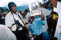 """Haiti. Province of Ouest. Port-Au-Prince.  Political demonstration by the supporters """" chimères"""" of the president of Haiti,  Jean-Bertrand Aristide and his political party, called Lavalas. They ask with their five fingers wide open that  the actual president Jean-Bertrand Aristide remains in power for the next five years. A picture of Jean-Bertrand Aristide, as a man of peace with both his hands open for the county and the haitian flag, is shown by the demonstators as a symbol of loyalty and continuity for the future of Haiti. The police controls the good progress of the demonstration by prohibiting any disorders and clashes with the supporters of the 184 group (opposition to Aristide).  © 2003 Didier Ruef"""