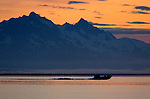 A jet bowpicker used for commercial fishing salmon, cruises across the Copper River delta on Alaska's north gulf coast against a colorful sunrise.