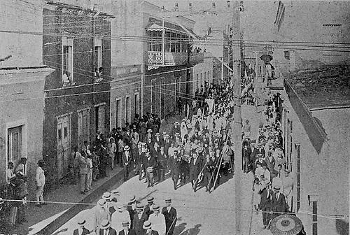 """""""Salida de la urna, en hombros de distinguidos discípulos de Hostos"""". © Delgado Brea, 1903."""