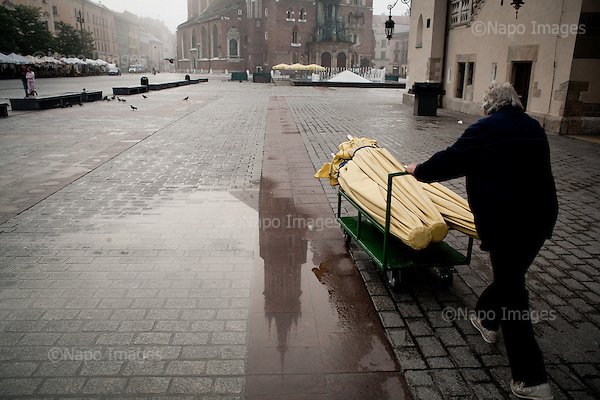 KRAKOW, POLAND, SEPTEMBER 12, 2011:.Main square in central Krakow with tower of Mariacki church reflecting in a paddle..(Photo by Piotr Malecki / Napo Images) ..KRAKOW, 9/2011:.Stary Rynek..Fot: Piotr Malecki / Napo Images