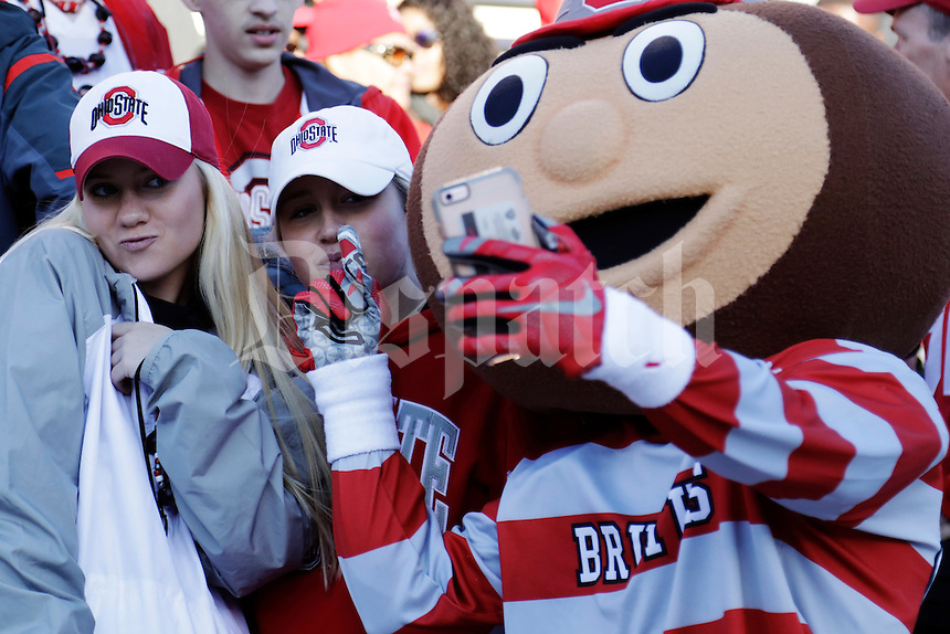 Ohio State fans Jordan Abaramczyk, left, and Emma Looney, center, both of Centerville, Virginia, take a selfie with Brutus the Buckeye before a NCAA Division I college football game between the Ohio State Buckeyes and the Maryland Terrapins on Saturday, November 12, 2016 at Maryland Stadium in College Park, Maryland. (Joshua A. Bickel/The Columbus Dispatch)