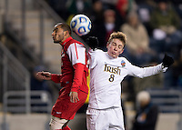 Nick Besler (8) of Notre Dame goes up for a header with Michael Calderon (11) of New Mexico during the NCAA Men's College Cup semifinals at PPL Park in Chester, PA.  Notre Dame defeated New Mexico, 2-0.