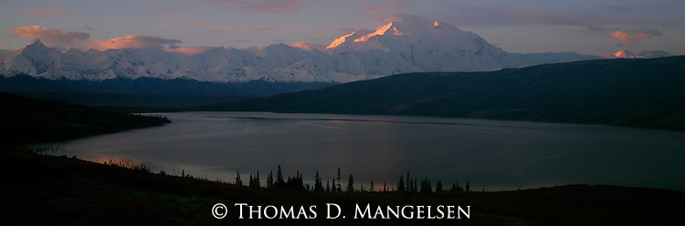 At the brink of dawn, the rising sun traces the outline of Mt. McKinley, the highest mountain on the North American continent.<br /> Denali National Park, Alaska