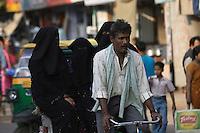 Rickshaw wallah or puller with three robed women in back. Varanasi, Uttar Pradesh, India