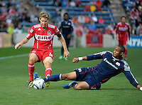 New England defender Darrius Barnes (25) slide tackles the ball away from Chicago midfielder Logan Pause (12).  The Chicago Fire defeated the New England Revolution 3-2 at Toyota Park in Bridgeview, IL on Sept. 25, 2011.