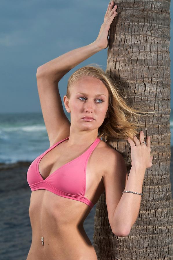 Young Cuacasian Woman in bikini posing in the beach.