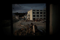 Ruins are seen through the broken window of a civic hall in Rikuzentakata April 2, 2011. According to a survivor and local media, after earthquake and tsunami warning between 60 and 100 people found shelter at civic hall building, designated as an evacuation shelter in the case of tsunami. Only eleven were rescued by a Japan's Self Defense Force helicopter, one of survivors said.    REUTERS/Damir Sagolj (JAPAN)