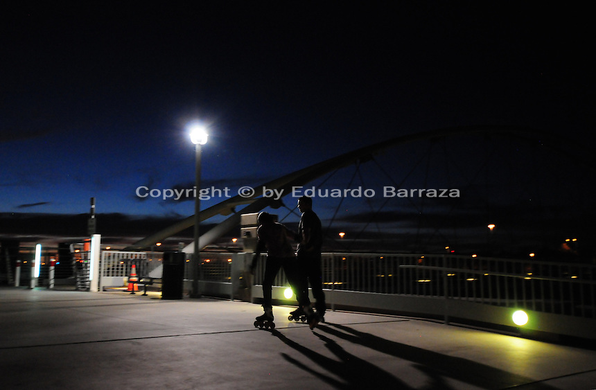 Tempe, Arizona. Two teenagers have some fun using skates to stroll by the lake. The artificial lake is a reservoir on a segment of the currently dry riverbed of the Salt River. The new dam will be a cost-effective solution expected to last for decades. The construction is called Town Lake Western Dam Replacement Project. Photo by Eduardo Barraza © 2015