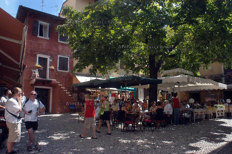 LAGO DI GARDA, Malcesine, turisti a un bar nel  centro storico.GARDA LAKE, Malcesine, tourists in the old town centre.