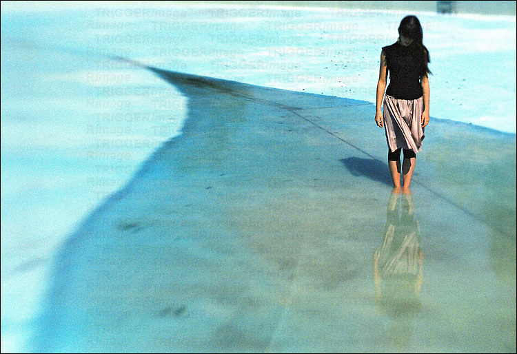 A teenage girl standing in an empty swimming pool under summer sun