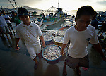Workers unload fish at sunrise in the harbor of Estancia, a village in the Philippines that was hit hard by Typhoon Haiyan in November 2013. The storm was known locally as Yolanda. The ACT Alliance has been active assisting residents of this town to recover from the typhoon.