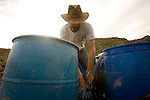 Rob Goreham pumping water from three tanks which he uses to pan a sample of  soil, Saturday, February 28, 2009. Rob is a  professional Gold Miner who runs complex gold mining operations..