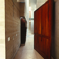 A massive pivotal wooden door opens onto a minimalist interior revealing concrete walls which have been left purposefully textured and imperfect