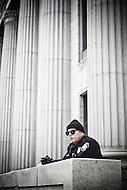 Federal police officer watches protesters from Federal courthouse steps.  Tim DeChristopher is facing ten years in prison on two felony charges for derailing an illegal sale of public land from the outgoing Bush administration to private oil and gas developers.