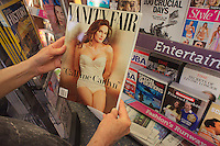 A reader browses a copy of the latest Vanity Fair magazine at a newsstand in New York, featuring Caitlyn Jenner, formerly Bruce Jenner on the cover and in a photo spread inside. (© Richard B. Levine)