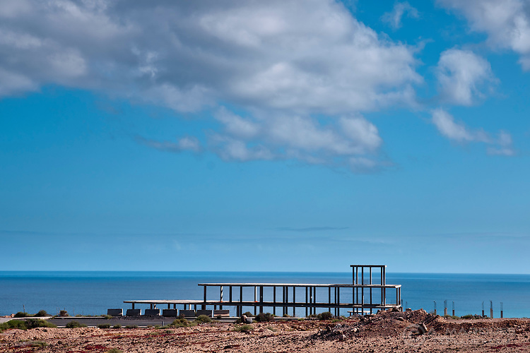 Incomplete construction, Fuerteventura, Canary Islands, Spain. The Island is punctuated by many incomplete constructions. The holiday and property market was booming a few years ago on the island - until some years before known as the island no-one goes to - but many construction sites were abandoned due to financial or legal reasons when the financial crisis hit. What remains are skeletons left to rot, and a testimony of what greed and uncontroled turism create.