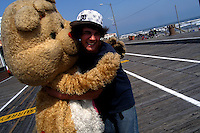 A teenager hugs a furry dressed as Tenderheart Bear on the boardwalk in Ocean City, New Jersey.   Furries are a group of people who identify themselves not as being human but as a walking, talking animal.  For some the lifestyle is complete, animal traits reach into every aspect of life from mundane trips to a grocery store to sexual fantasies.  For others, involvement in the furry fandom is limited to public performances and meet-and-greets.