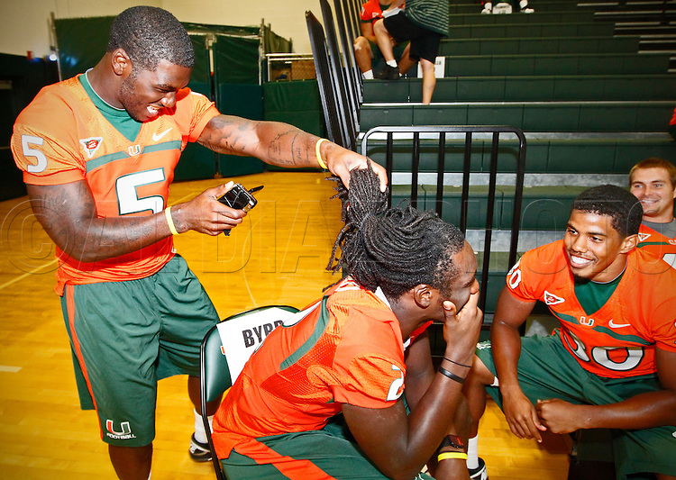 Mike Jakes shoots video of the back head of teammate LaRon Byrd as AJ Highsmith interviews the player during Media Day for the University of Miami Football team on Campus in Coral Gables on August 27, 2011.
