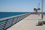 Four Women walking along the Harbour Wall Pier Promenade Walk in Alicante, Spain