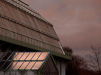 Tropical Rainforest Glasshouse (formerly Le Jardin d'Hiver or Winter Gardens), 1936, René Berger, Jardin des Plantes, Museum National d'Histoire Naturelle, Paris, France, and alongside it the Desert and Arid Land Glasshouse. Low angle view of the roofs at twilight.