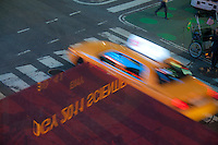 Blurred taxi in motion and stockinfo reflection on Times Square, New York City