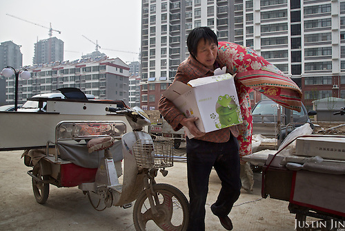 Chen Hua, 50, moves into her new urban home in a northeastern China.<br /> <br /> Her former village house was bulldozed by the government three years ago to make way for high-rise development. <br /> <br /> In the four years between her rural home being razed and the completion of her new city apartment, she and her family lived in temporary village housing such as this one. <br /> <br /> China is pushing ahead with a dramatic, history-making plan to move 100 million rural residents into towns and cities between 2014 and 2020 &mdash; but without a clear idea of how to pay for the gargantuan undertaking or whether the farmers involved want to move.<br />