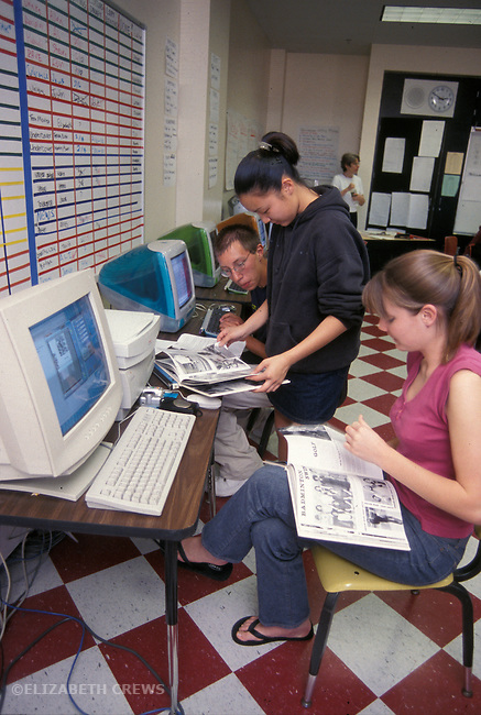 Albany CA Highschool journalism students working on year book, researching in previous years' books
