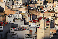 View of the town of Moulay Idriss, over rooftops of houses with flat roofs with the minaret of the Mausoleum of Moulay Idriss I in the foreground, Meknes-Tafilalet, Northern Morocco. The town sits atop 2 hills on Mount Zerhoun and was founded by Moulay Idriss I, who arrived in 789 AD and ruled until 791, bringing Islam to Morocco and founding the Idrisid Dynasty. It is an important pilgrimage site for muslims. Picture by Manuel Cohen
