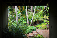 Brick steps and patio in Don Worth tropical foliage garden with palm trees viewed / framed by entry walls and breezeway
