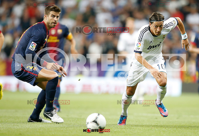 Real Madrid's Mesut Özil against Barcelona's Gerard Pique during Super Cup match. August 29, 2012. (ALTERPHOTOS/Alvaro Hernandez). NortePhoto.com
