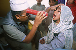 An Afghan refugee girl is examined by a physician from the Islamic Relief Society upon crossing the border at Chaman into Pakistan..