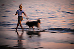 A blurred woman and her dog in motion during sunset on a beach