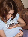 Pre-teen girl playing with pet mouse