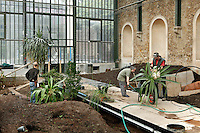 New Caledonia Glasshouse (formerly The Mexican Hothouse), 1830s, Charles Rohault de Fleury, Jardin des Plantes, Museum National d'Histoire Naturelle, Paris, France.  Low angle view of gardeners replanting the glasshouse. They have filled the new beds on both sides of the waterfall with earth and are now putting in the plants on either side of the central walkway. Through the windows the Plant History Glasshouse (formerly Australian Glasshouse), 1830s, Rohault de Fleury, is visible. The New Caledonia Glasshouse, or Hothouse, was the first French glass and iron building.