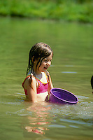 Young girl standing in pond on hot summer day  holding a plastic purple bucket