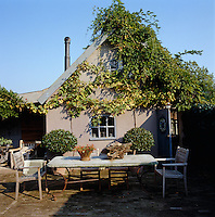 Wisteria and vines cover the walls and buildings surrounding this courtyard which provides an idyllic setting for dining al fresco